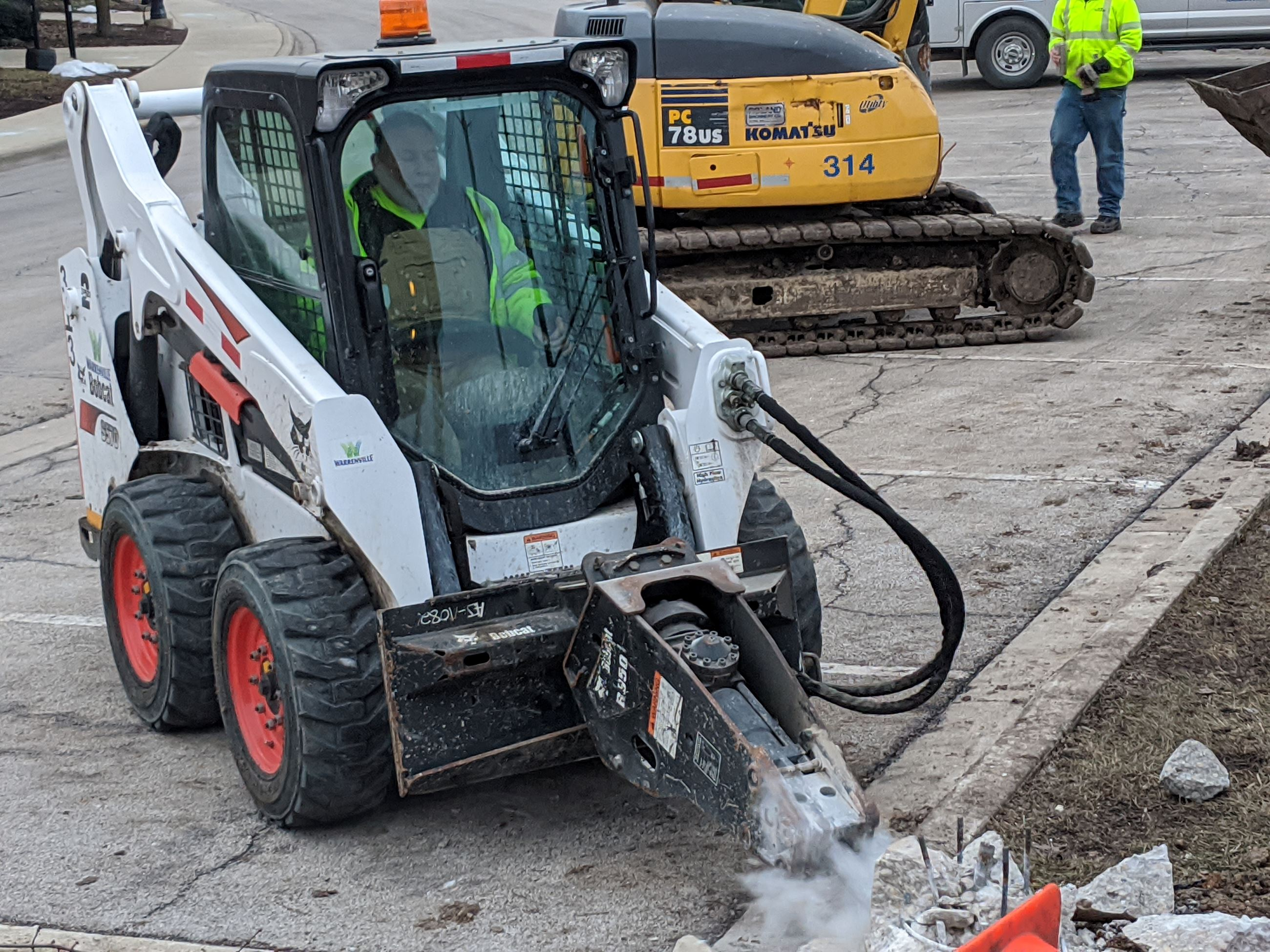 Photo of Streets Division Staff Operating a Bobcat to Break Concrete